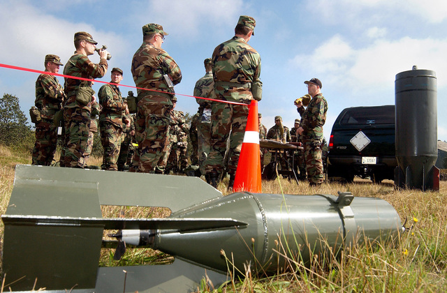 U.S. Air Force TECH. SGT. James Widmark (right), 62nd Civil Engineer Squadron, Explosive Ordnance Disposal Flight, briefs Airmen from the 62nd Medical Group on identifying various explosive ordnances such as the bomb in the foreground. The briefing, given during an Ability to Survive and Operate Training session on McChord Air Force Base, Wash., trains Airmen on how to identify and respond to unexploded ordnances. (U.S. Air Force photo by Kristin Royalty, CIV) (Released)
