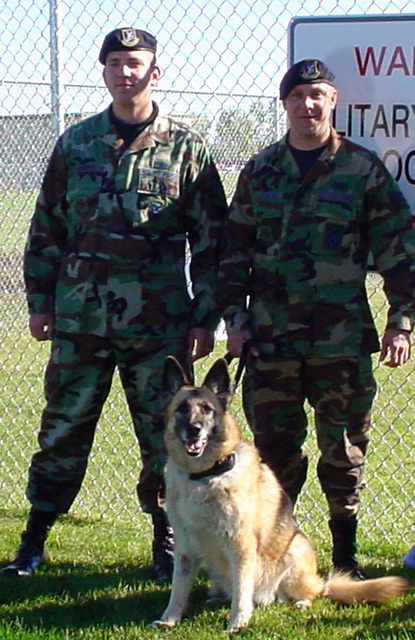 U.S. Air Force STAFF Sgts. (left to right) Dan Casetta and Michael Laughlin, Military Working Dog Handlers, 319th Security Forces Squadron, 319th Mission Support Group, 319th Air Refueling Wing, pose with Anet, a Military working Dog, outside the 319th SFS kennel training area, on Grand Forks Air Force Base, N.D., on Sept. 28, 2004. (U.S. Air Force PHOTO by STAFF SGT. Scott T. Sturkol) (Released)