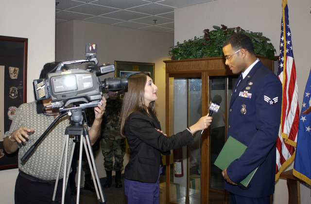 A local Television Reporter (center) interviews Georgia Air National Guard SENIOR AIRMAN Charles Simpson (right), 116th Air Control Wing, on Sept. 29, 2004, at a ceremony held at Warner Robins Air Force Base, Ga., to recognize SENIOR AIRMAN Simpson for his role in aiding at the scene of a serious traffic accident, while on his way home from a drill weekend. SENIOR AIRMAN Simpson holds a book on the history of the City of Warner Robins that was presented to him by the Honorable Donald S. Walker (right), Mayor of the City of Warner Robins, Ga., in recognition for his efforts. (U.S. Air Force photo by MASTER SGT. Rick Cowan) (Released)