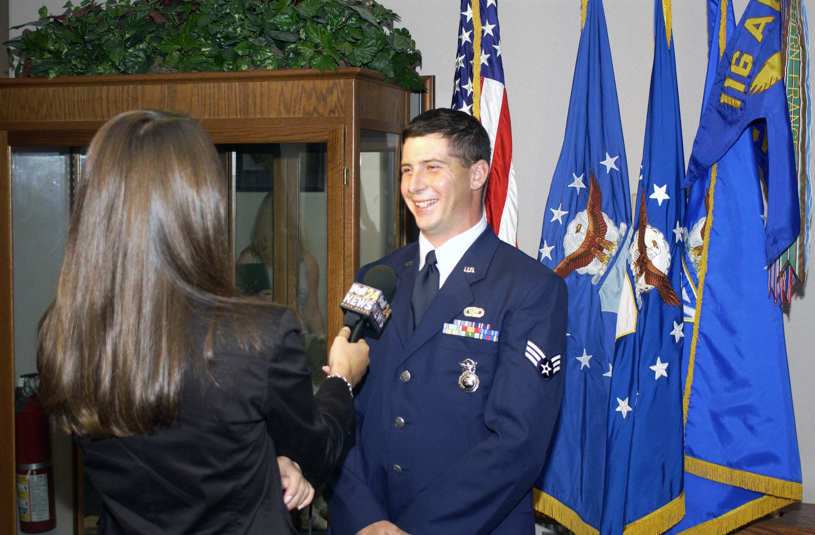 A local television reporter (left) interviews Georgia Air National Guard SENIOR AIRMAN Joe Ciancio (right), 116th Air Control Wing, on Sept. 29, 2004, at a ceremony held at Warner Robins Air Force Base, Ga., to recognize SENIOR AIRMAN Ciancio for his role in assisting at the scene of a serious traffic accident. (U.S. Air Force photo by MASTER SGT. Rick Cowan) (Released)