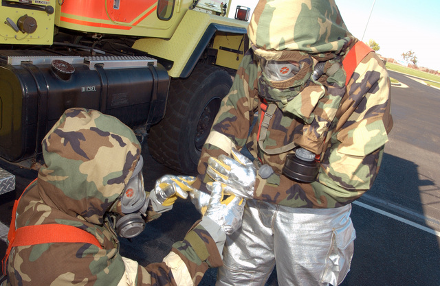 South Dakota Air National Guard 114th Fighter Wing personnel use the buddy system while the don their Mission-Oriented Protective Posture response level 4 (MOPP-4) gear on Oct. 2, 2004, during an Operation Readiness Exercise being conducted at Joe Foss Field in Sioux Falls, S.D. (U.S. Air Force photo by STAFF SGT. Michael Frye) (Released)