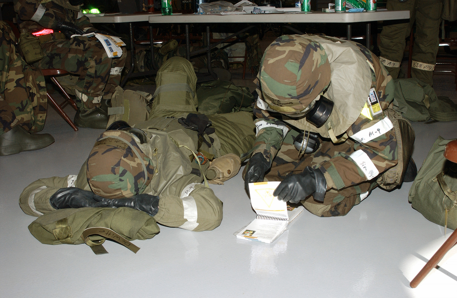 South Dakota Air National Guard TECH. SGT. Chris Novak (right) consults the manual about the proper procedure to administer an atropine injection to TECH. SGT. Scott DeWitt (left), both with Pod A, 114th Fighter Wing, during a simulated Mission-Oriented Protective Posture response level 4 (MOPP-4) gear exercise on Oct. 2, 2004, during an Operation Readiness Exercise being conducted at Joe Foss Field in Sioux Falls, S.D. (U.S. Air Force photo by MASTER SGT. Scott H. Leebens) (Released)