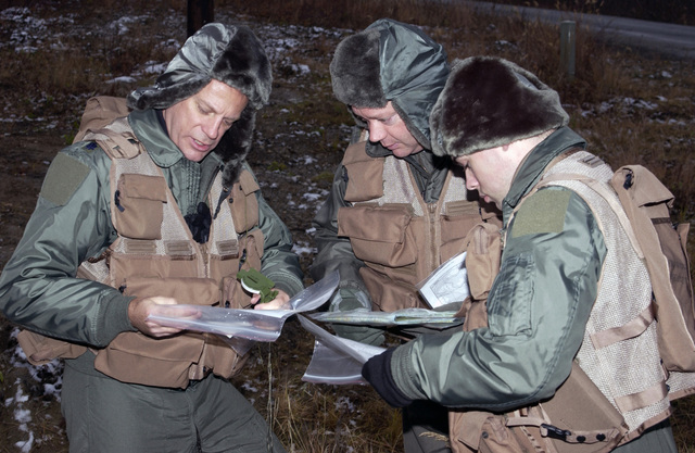 Alaska Air National Guard LT. COL. Dean Armstrong (left), MAJ. Jim Fitts (center), and SENIOR AIRMAN Brian Binkley (right), all with the 168th Air Refueling Wing, review their maps as they participate in simulated bailout over enemy territory map reading and compass use scenario on Oct. 3, 2004, during a Combat Survival Task evaluation being conducted on Eielson Air Force Base, Alaska. (U.S. Air Force photo by SENIOR AIRMAN Joshua Strang) (Released)