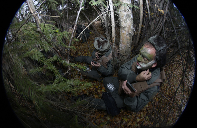 Alaska Air National Guard LT. COL. Dean Armstrong (right) and SENIOR AIRMAN Brian Binkley (left), both with the168th Air Refueling Wing, apply camouflage face paint as the participate in a simulated bailout over enemy territory map reading and compass use scenario on Oct. 3, 2004, during a Combat Survival Task evaluation being conducted on Eielson Air Force Base, Alaska. (U.S. Air Force photo by SENIOR AIRMAN Joshua Strang) (Released)