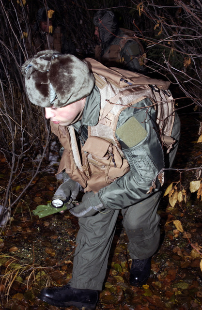 Alaska Air National Guard SENIOR AIRMAN Brian Binkley, 168th Air Refueling Wing, studies a compass as he leads a three-man team to a safe area in a simulated bailout over enemy territory map reading and compass use scenario on Oct. 3, 2004, during a Combat Survival Task evaluation being conducted on Eielson Air Force Base, Alaska. (U.S. Air Force photo by SENIOR AIRMAN Joshua Strang) (Released)