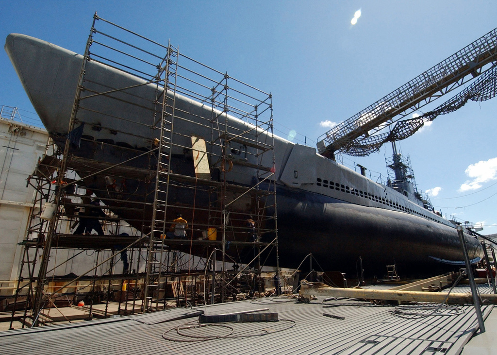 Marisco Ltd. workers repair the aging hull of the decommissioned Balao Class Submarine BOWFIN (SS 287) in a floating dry dock at their shipyard near the former Naval Air Station (NAS) Barber's Point, Hawaii (HI), during a restoration project. BOWFIN served as a floating museum for 23 years, and is moored next to the battleship USS ARIZONA (BB 39) Memorial visitor's center. Known as the Pearl Harbor Avenger, the BOWFIN was launched one year to the day after the December 7th, 1941 attack. The ship is credited with sinking 44 enemy ships during the course of her nine extraordinary war patrols