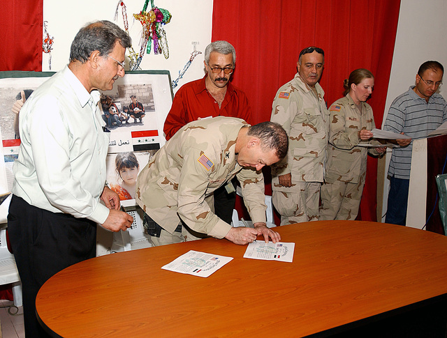 U.S. Army COL. Stephen R. Lanza, Commander 5th Brigade Combat Team/1ST Cavalry Division, signs an agreement linking schools in the United States with Iraqi schools as part of a program to rebuild the education system with supplies and educational materials in Baghdad, Iraq, on Oct. 6, 2004, in support of Operation IRAQI FREEDOM.  (U.S. Air Force PHOTO by TECH. SGT. R. Nick Siers) (RELEASED)