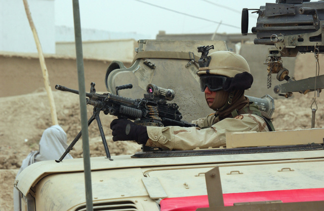 US Army (USA) SPECIALIST (SPC) Robert Hollett, assigned to Headquarters and Headquarters Company (H&HC), 2nd Battalion, 35th Infantry Regiment, 25th Infantry Division, stands ready with his 5.56mm M249 Squad Automatic Weapon (SAW) during a vehicle mounted patrol in Qalat, Afghanistan, during the first national democratic elections ever to be held in Afghanistan, during Operation ENDURING FREEDOM