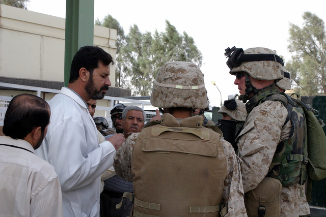 US Marine Corps (USMC) Captain (CPT) Eric Dougherty (right), Commanding Officer (CO), Echo Company (E Co.), 2nd Battalion (BLT), 5th Marine Regiment, 1ST Marine Division (MARDIV), speaks with Dr. Akmed Rahim, Pediatrician and Assistant Director of the Womens and Childrens Hospital, Ar Ramadi, Al Anbar Province, Iraq, about what his unit can do to assist the hospitals efforts to improve the health care for the patients. The 1ST MARDIV is involved in a Security and Stabilization Operation (SASO) in Ar Ramadi during Operation IRAQI FREEDOM