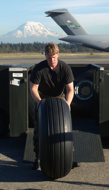 U.S. Air Force AIRMAN 1ST Class Caleb Blood, crew chief, 62nd Aircraft Maintenance Squadron, pushes out a brand new front landing tire at McChord Air Force Base, Wash., On Oct. 12, 2004. (U.S. Air Force PHOTO by Kevin Tosh, CIV.) (Released)