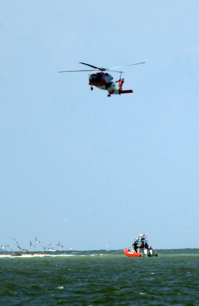 A U.S. Coast Guard HH-60J Jayhawk search and rescue helicopter, watches for stray boaters in a detonation containment area, as a MacDill Air Force Base Explosive Ordnance Distposal Team prepares to disembark a rigid-hull inflatable boat at Passage Key Island, Fla., on Oct 13, 2004.(U.S. Air Force PHOTO by STAFF SGT. Chad Chisholm) (Released)