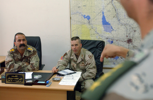 U.S. Army LT. COL. Mark Strong (center) meets with Iraqi LT. COL. Ali Mohammed Darwis Kaki (left), and his staff at the Iraqi National Guard headquarters located at Camp Caldwell during a joint staff meeting, on Oct. 13, 2004, in support of Operation IRAQI FREEDOM.(U.S. Air Force PHOTO by SENIOR AIRMAN Christopher A. Marasky) (Released)