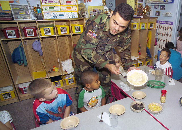 U.S. Army MAJ. Javier Garcia, Defense Equal Opportunity Management Institute, Patrick Air Force Base, Fla., serves festive snacks to the toddlers at the Child Development Center while promoting Hispanic American Culture Day on Oct. 15, 2004. (U.S. Air Force photo by Jim M. Laviska) (Released)