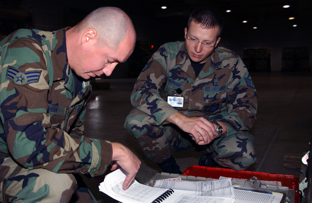 U.S. Air Force SENIOR AIRMAN Theodore Hogan (left), 99th Logistics Readiness Squadron, discusses cargo paperwork requirements with STAFF SGT. Michael Kauffman, 99th Medical Support Squadron, Oct. 16, 2004, during an Operational Readiness Inspection at Nellis Air Force Base, Nev. (U.S. Air Force PHOTO by MASTER SGT. Robert W. Valenca) (Released)