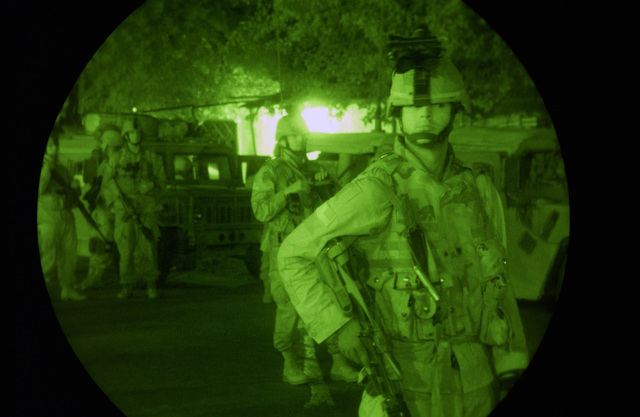 Night vision view of U.S. Army Soldiers, Alpha Troop, 1ST Squadron, 4th Cavalry Regiment (1-4 CAV), 1ST Infantry Division (ID), conduct a security mission during Operation Duluyiah Sunrise on Oct. 18, 2004, at Forward Operating Base McKenzie, Al Anbar Province, Iraq.  Operation Duluyian Sunrise is a joint operation between the 1-4 CAV and the Iraqi Ministry of Interior Special Police for the apprehension of key black list personnel organizing anti-iraq forces carrying out attacks against Coalition Forces in and around the Ad Duluyiah area.  (U.S. Air Force photo by STAFF SGT. Shane A. Cuomo) (Released)