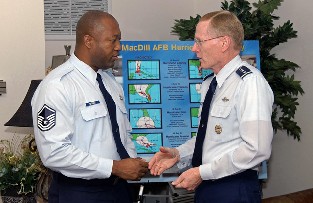 U.S. Air Force GEN. John W. Handy (right) Commander, U.S. Transportation Command, and Commander, Air Mobility Command, presents a coin to MASTER SGT. Wesley D. Mathias (left) for outstanding weather support during the 2004 hurricane season at MacDill AFB, Fla., on Oct. 20, 2004.(U.S. Air Force PHOTO by AIRMAN 1ST Class Jason Robertson) (RELEASED)