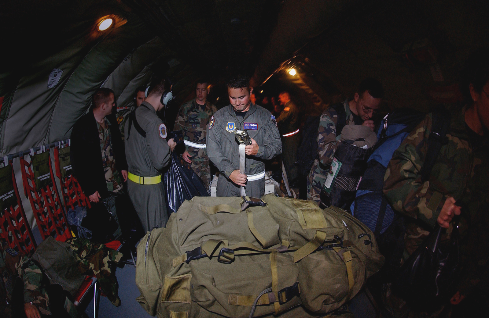 U.S. Air Force STAFF SGT. J.L. Smith, Boom Operator, 351st Air Refueling Squadron, 100th Air Refueling Wing, tightens down a strap to secure baggage before departing from RAF Mildenhall, U.K., on Oct. 20, 2004.(U.S. Air Force PHOTO by AIRMAN 1ST Class Franklin J. Perkins) (RELEASED)