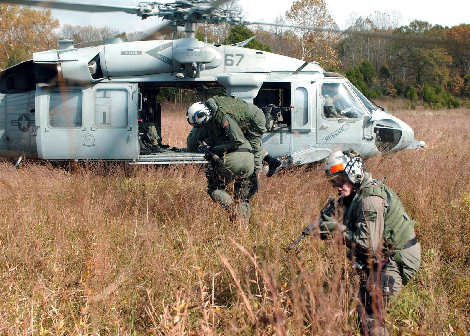 US Navy (USN) Aviation Ordnanceman Third Class (AO3) Rabea Shaiboon (foreground) stands ready to provide cover fire armed with a 5.56 mm M4 carbine, as USN Aviation Electronics Technician Second Class (AT2) Derek Nord, carries a downed aviator to a waiting MH-60S KnightHawk helicopter, from Helicopter Combat Support Squadron Six (HC-6), during urban assault and combat Search And Rescue (SAR) training with USN SEAL (Sea, Air, Land) team members at Fort Knox, Kentucky (KY)