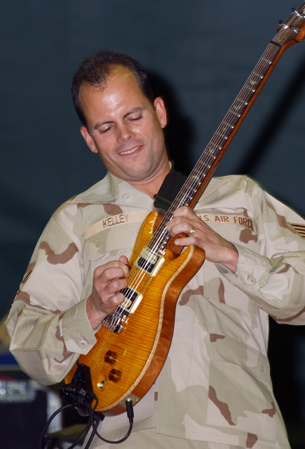 """U..S. Air Force STAFF SGT. Jerry Kelly, a bass player with the Band of the Pacific's, Topcover Band, plays to students at Service High School, Anchorage, Alaska, on Oct. 21, 2004 in support of""""Red Ribbon Week'. (U.S. Air Force PHOTO by SSgt Rhiannon Willard) (RELEASED)"""