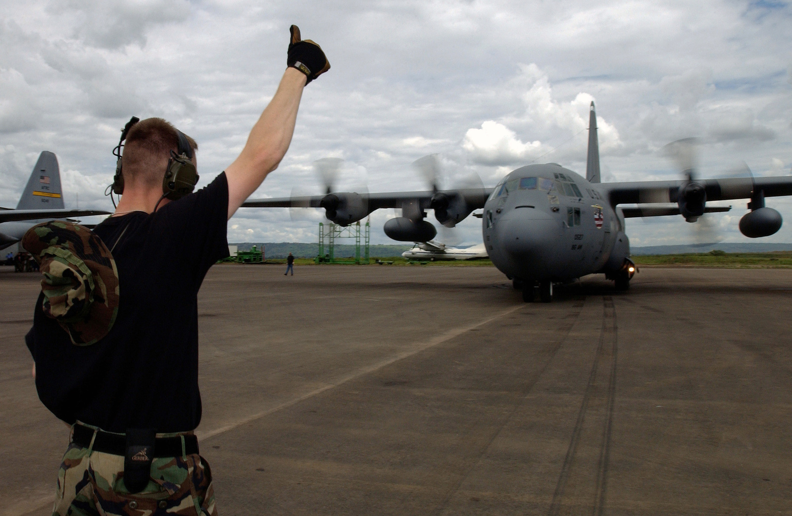 U.S. Air Force STAFF SGT. Justin Niederhofer, crew chief, 86th Airlift Maintenance Squadron, 86th Airlift Wing, assigned to the 322nd Air Expeditionary Group, marshals a U.S. Air Force C-130 Hercules cargo aircraft at the Kigali International Airport, Rwanda, in support of Operation Silverback Express, on Oct. 23, 2004.(U.S. Air Force PHOTO by STAFF SGT. Tony R. Tolley) (RELEASED)