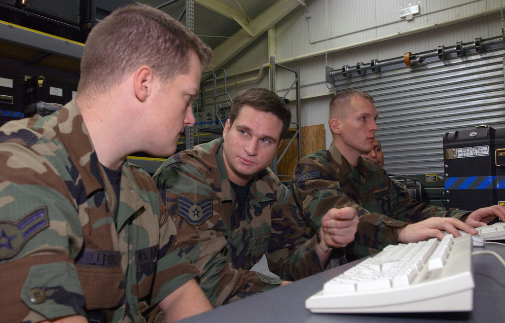 From left to right:  U.S. Air Force AIRMAN 1ST Class Nicholas Willford, a Computer Operator Systems Technician, works with STAFF SGT. Brandon Lambert, NCOIC of Data Systems, to install a firewall to the network, while SENIOR AIRMAN Tobias Salloum, a Network Administrator, installs a Microsoft exchange to the email server, during 31st Communication Squadron's Air Expeditionary Communications Element training here at Aviano Air Base, Italy, on Oct. 25, 2004.(U.S. Air Force PHOTO by STAFF SGT. Lakisha Croley) (RELEASED)
