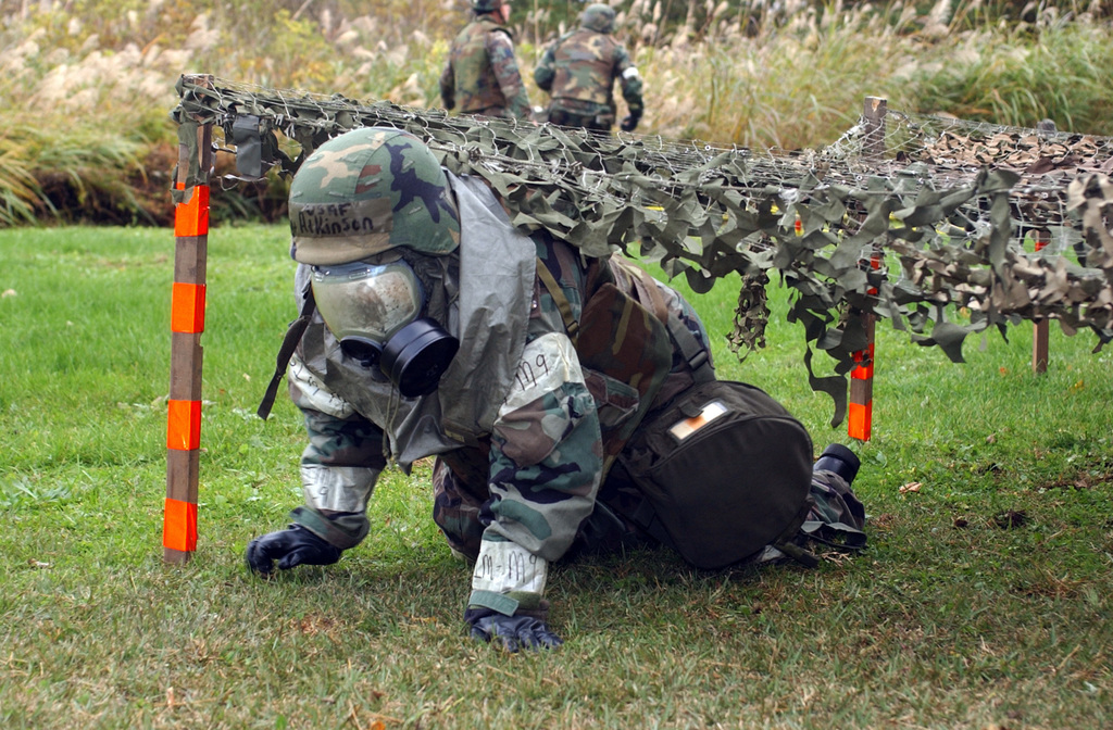 U.S. Air Force SENIOR AIRMAN Tiana Atkinson, 301st Intelligence Squadron, dressed in chemical gear, crawls under a net at Misawa Air Base, Japan, during an obstacle course on the annual Warrior Day competition, on Oct. 26, 2004.(U.S. Air Force PHOTO by STAFF SGT. Andy Bellamy) (RELEASED)