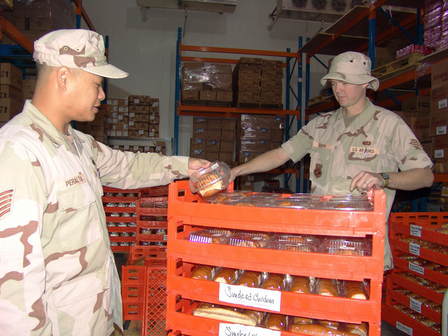 U.S. Air Force TECH. SGT. Ernest Peralta (left) and SENIOR AIRMAN Steven Narick, both members of the Expeditionary Services Squadron, check the expiration date on crates of sandwiches at the dining facility at an undislosed forward deployed location on Oct. 26, 2004. (U.S. Air Force photo by CAPT Aaron Burgstein) (Released)