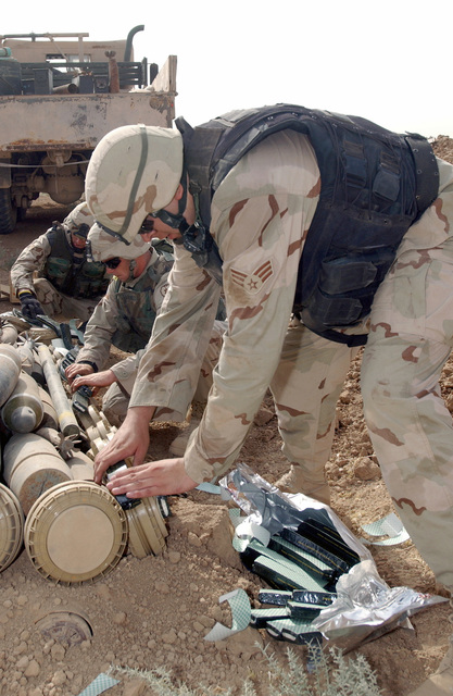 U.S. Air Force SENIOR AIRMAN Randall Peterson (right), an Explosive Ordnance Disposal (EOD) specialist from the 506th Expeditionary Civil Engineer Squadron, together with two unidentified military personnel unload live munitions at Kirkuk Air Base, Iraq, on Oct. 28, 2004. He is deployed here from the 52nd Civil Engineer Squadron, Explosive Ordanance Disposal Flight at Spangdahlem Air Base, Germany. (USAF PHOTO by STAFF SGT. Adrian Cardiz) (Released)