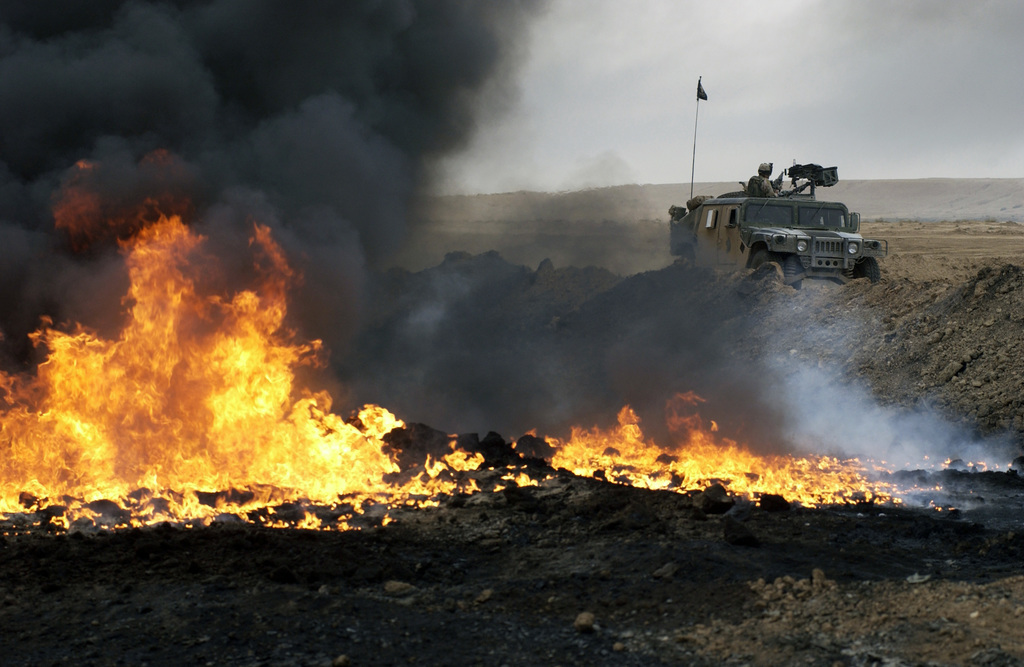 A U.S. Army Soldier provide security from the turret of his High-Mobility Multipurpose Wheeled Vehicle (HMMWV) near burning oil after insurgents attack an oil pipeline near Bayji, Iraq, on Oct. 30, 2004. (USAF PHOTO by TECH. SGT. Lee Harshman) (Released)