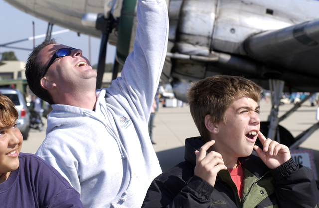 Tony Wilkins watches aircraft perform stunt maneuvers while his son, Nathan, 11, covers his ears to dampen the intense jet engine noise at Vandenberg Air Force Base, Calif., on Oct. 31, 2004. The event is part of the Westen Air and Space Show that is held biannually here to demonstrate the capabilities of both modern and vintage aircraft and the pilots that fly them. (USAF PHOTO by AIRMAN 1ST Class Barry Loo) (Released)