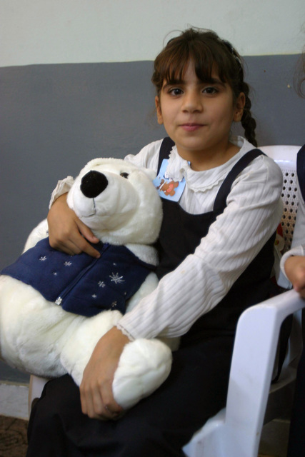 A young girl smiles after receiving a large, stuffed teddy-bear as a gift from US Marine Corps (USMC) Marines, Alpha Company (A CO), Battalion Landing Team (BLT), 1ST Battalion (BN), 4th Marine Regiment, 11th Marine Expeditionary Unit (MEU), Special Operations Capable (SOC). She is an orphan at the Aleskan Orphan House for Children in Ad Diwaniyah, Iraq. A CO Marines and 404th BN, 50th Iraqi National Guard (ING) BN Soldiers visited the orphanage to distribute toys to the children during Operation IRAQI FREEDOM