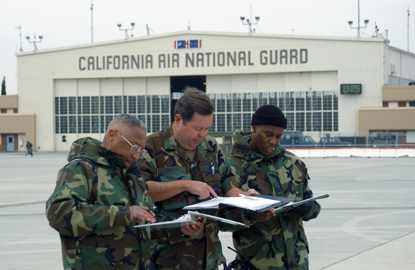 CAPT. Charles Hall (right), SENIOR MASTER SGT. Brad Winter (center), and CHIEF MASTER SGT. Willis Mucelroy (left), all members of the 144th Fighter Wing, Maintenance Operation Center, California Air National Guard, review a flight schedule during an Operation Readiness Exercise at Fresno Air National Guard Base at Fresno Yosemite International Aiport, Calif., on Nov. 3, 2004. (USAF PHOTO by MASTER SGT. Matthew P.Millson) (Released)