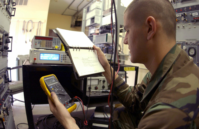 U.S Air Force AIRMAN 1ST Class Scott Ponte, a ground radio communications apprentice, refers to an abbreviated Technical Orders (TO) while taking readings on a digital multi-meter during a scheduled inspection on a GRR-22 Radio Receiver at Mount Lemmon, Tucson, Ariz., on Nov. 5, 2004. He is assigned to the 355th Communications Squadron at Davis-Monthan Air Force Base, Ariz. (USAF PHOTO by AIRMAN 1ST Class Christina D. Kinsey) (Released)