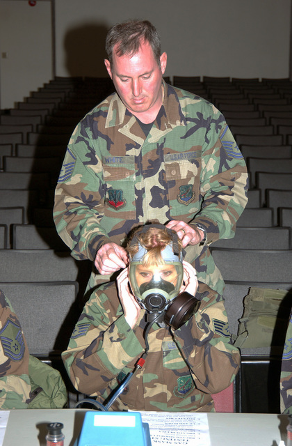 MASTER SGT. White assists STAFF SGT. Becky Nelson, a graphics specialist, with her gas mask during drill weekend at Gowen Field, Boise, Idaho, on Nov. 6, 2004. Both are members of the 124th Wing, Idaho Air National Guard. (USAF PHOTO by SENIOR AIRMAN Heather Walsh) (Released)