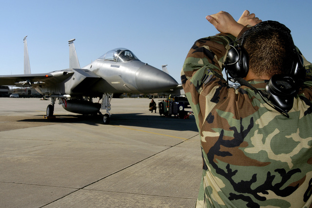 U.S. Air Force SENIOR AIRMAN Raynard Tsukiyama, an F-15C Eagle aircraft crew chief from the 19th Fighter Squadron, Elemendorf Air Force Base, Alaska, marshals out his aircraft during exercise William Tell 2004 at Tyndall Air Force Base, Fla., Nov. 8, 2004. This is the 50th Anniversary of the William Tell competition, an exercise that tests an aircrew's ability to perform under combat conditions. (USAF PHOTO by STAFF SGT. Kenny Kennemer) (Released)