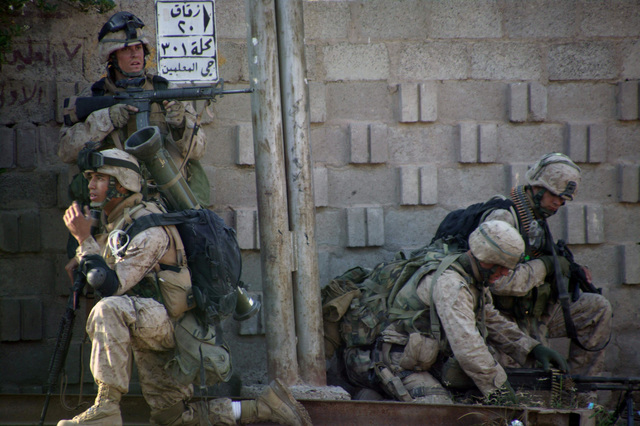 Four US Marine Corps (USMC) Marines, 1ST Battalion (BN), 8th Marine Regiment (1/8), remain at the ready on a street corner during combat operations with insurgents during a Security and Stabilization Operation (SASO) conducted as part of Operation AL FAJR, which is an offensive operation to eradicate enemy insurgents in Fallujah, Al Anbar Province, Iraq, during Operation IRAQI FREEDOM