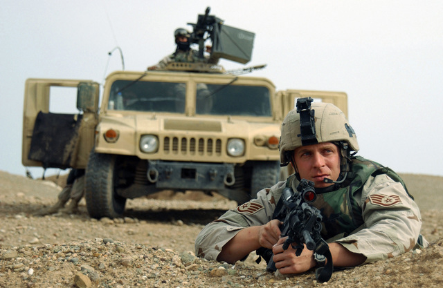 US Air Force (USAF) STAFF Sergeant (SSGT) David Howe, 823rd Security Forces Squadron (SFS), deployed with the 506th Expeditionary Security Forces Squadron (ESFS), Tactical Forces Flight (TFF) at Kirkuk AB, Iraq, readies his 5.56mm M4 Carbine as he scans a field near the base for any suspicious enemy activity, during Operation IRAQI FREEDOM