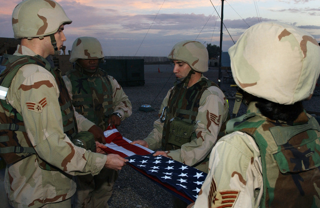 US Air Force (USAF) Airmen assigned to the 506th Expeditionary Medical Squadron (EMS) fold the American Flag during a Veteran's Day Retreat Ceremony at Kirkuk AB, Iraq, during Operation IRAQI FREEDOM