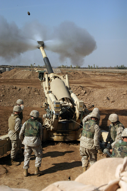 US Marine Corps (USMC) Marines assigned to Mike Battery, 4th Battalion, 14th Marines, engage enemy targets with their M198 155mm Towed Howitzer, at Camp Fallujah, Iraq during Operation IRAQI FREEDOM