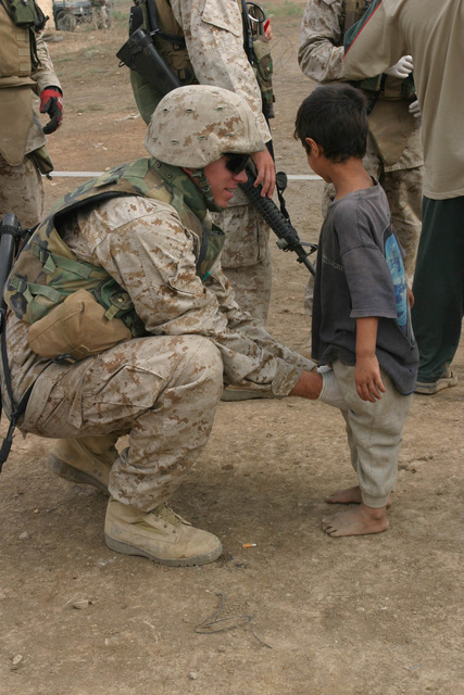 US Marine Corps (USMC) Corporal (CPL) Kevin A. Coe, Supply Clerk, Supply Detachment, Marine Expeditionary Unit Service Support Group 11 (MSSG-11), 11th Marine Expeditionary Unit (MEU) Special Operations Capable (SOC), pats down a young Iraqi child at the Entry Control Point (ECP) during a Humanitarian Assistance Operation (HAO) in the village of Ash Shafiyah, Iraq. This HAO provided medical and dental treatments to more than 100 Iraqis during Operation IRAQI FREEDOM