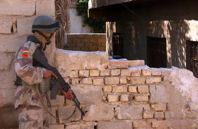 A soldier from the 6th Battalion, New Iraqi Army looks around a wall before enter the court yard before entering it during a raid on an suspected insurgent's house in Al Karmah, which is on the out skirts of Fallujah during combat operation on Nov. 15, 2004 during Operation Iraqi Freedom. (U.S. Army photo by SGT. 1ST Class Johancharles Van Boers) (Released)