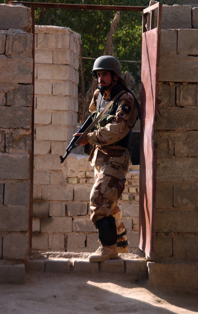 A soldier from the 6th Battalion, New Iraqi Army prepares to enter a doorway during a raid on an suspected insurgent's house in Al Karmah, which is on the out skirts of Fallujah during combat operation on Nov. 15, 2004 during Operation Iraqi Freedom. (U.S. Army photo by SGT. 1ST Class Johancharles Van Boers) (Released)