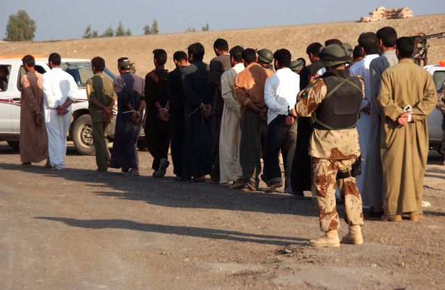 Soldiers from the 6th Battalion, New Iraqi Army lead the suspected insurgents to a holding area, which they will be turned over to the Americans for further processing during a raid on a suspected insurgent's house in Al Karmah, which is on the out skirts of Fallujah during combat operation on Nov. 15, 2004 during Operation Iraqi Freedom. (U.S. Army photo by SGT. 1ST Class Johancharles Van Boers) (Released)