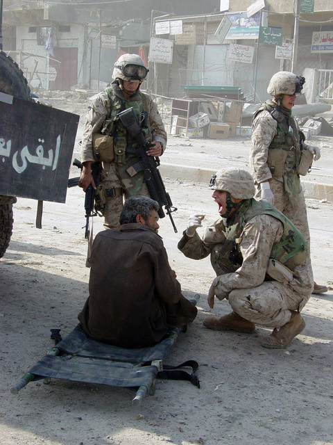 A U.S. Navy Corpsman assists a wounded Iraqi civilian found in the Al Jumhoria Medical Clinic, at Fallujah, Iraq, on the 16th of Nov. 2004, after Multinational forces pressed into the city to battle the entrenched insurgents. The civilian was tested for gunpowder residue but none was discovered, he was given food and water then taken to a Regimental Aid Station for examination. (U.S. Marine Corps PHOTO by CPL. Theresa M. Medina) (Released)