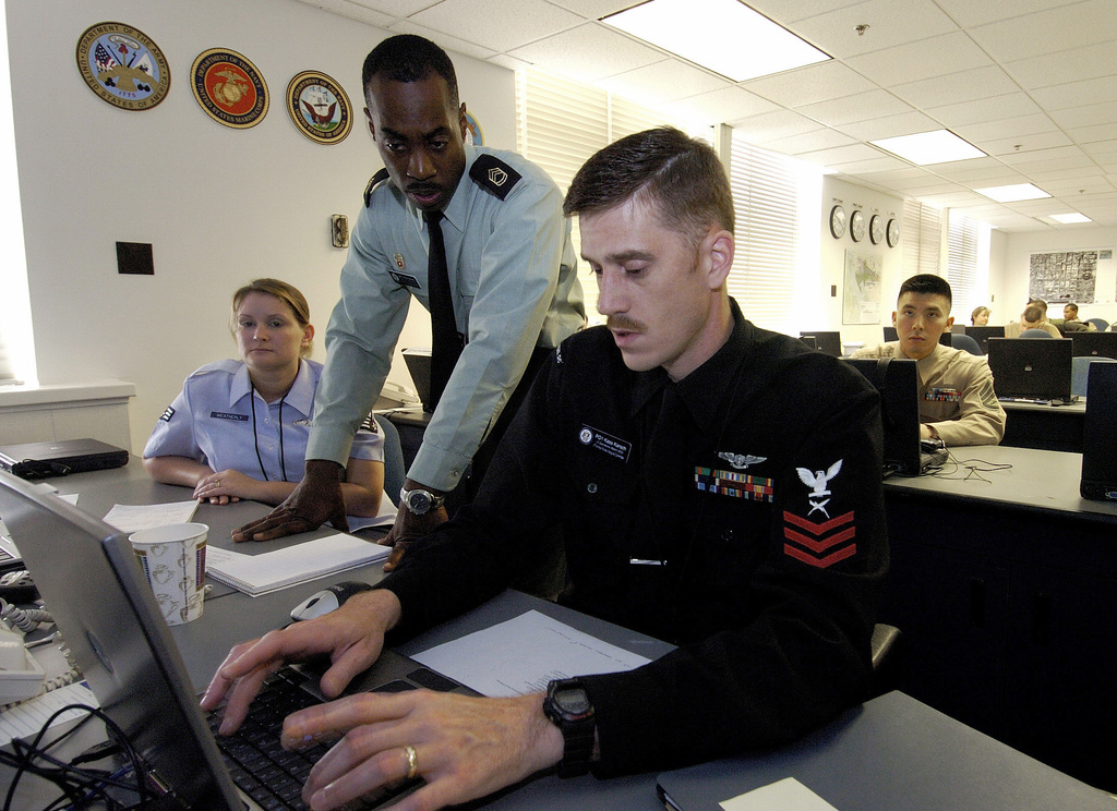 From left to right, U.S. Air Force SENIOR AIRMAN Jennifer Weatherly, U.S. Army SGT. 1ST Class Willie Warren observe U.S. Navy PETTY Officer 1ST Class Kass Karsch type on the computer during a Joint Task Force Armed Forces Inaugural Committee Operations Center exercise in Washington, D.C., on Nov. 16, 2004.(U.S. Air Force PHOTO by MASTER SGT. Mark A. Suban)(Released)