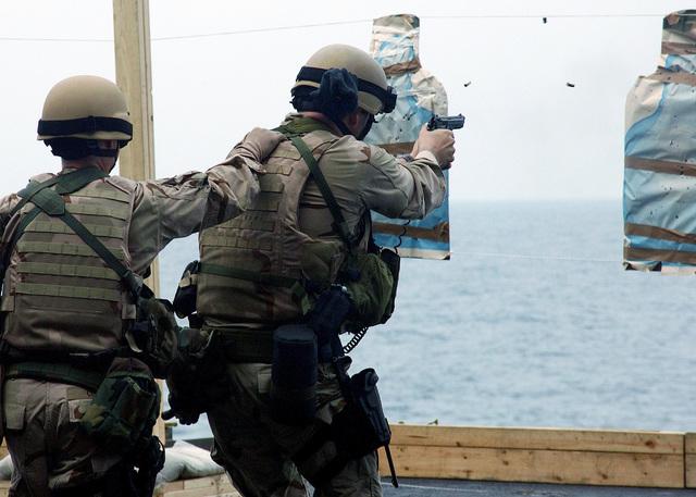US Navy (USN) MASTER-at-Arms Third Class (MA3) Adam Coleman (left) acts as a spotter behind Boatswain's Mate First Class (BM1) Jody Lanham from Explosive Ordnance Disposal Unit Six (EODMU-6), Detachment Ten, as he fires rounds from a 9mm handgun during a small arms live fire exercise aboard The Nimitz Class: Aircraft Carrier, USS HARRY S. TRUMAN (CVN-75)