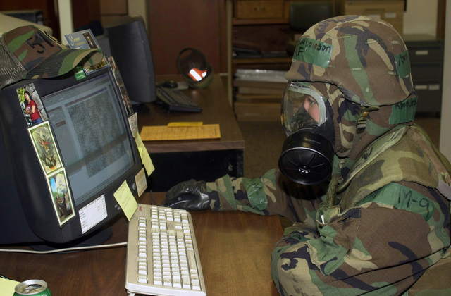 U.S. Air Force AIRMAN Jessica Lawson, a graphics specialist from the 51st Communication Squadron, works on a computer during training during the Wing Safety Day at Osan Air Force, Korea, on Nov. 17, 2004. She is attired in Mission Oriented Protective Posture (MOPP) Level 4. (USAF PHOTO by AIRMAN 1ST Kristi Mulder) (Released)