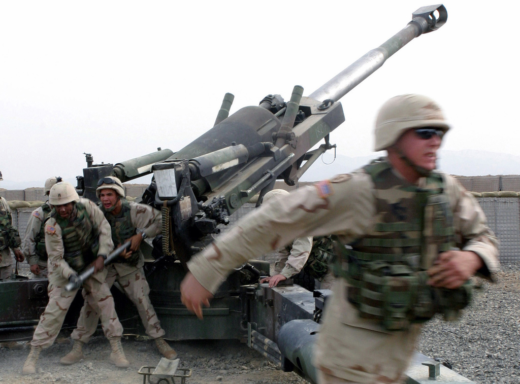 US Marine Corps (USMC) M-198 155mm Howitzer gun crew from Fox Battery, 7th Field Artillery, fire rounds down range during a fire mission exercise at Forward Operating Base (FOB) Salerno, Afghanistan (AFG), in support of Operation ENDURING FREEDOM