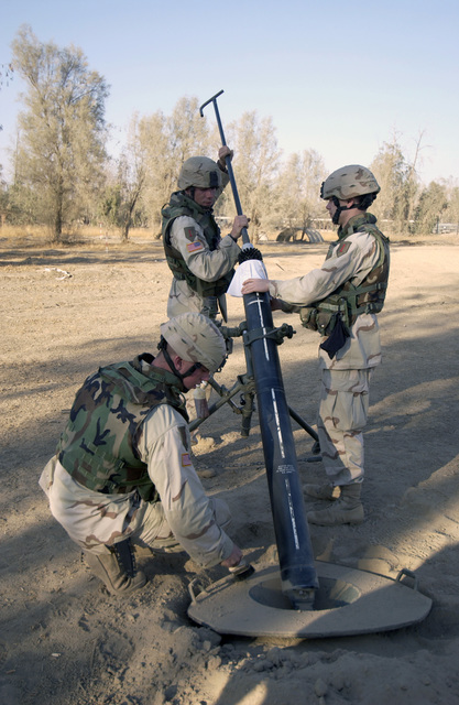 U.S. Army PFC. Class Mathew Taylor, SPC.Paul Sakala, and SPC. Ryan Benoist, all members of Charlie Troop, 1ST Squadron, 4th Cavalry Regiment, 1ST Infantry Division, clean the tube of their M120 120 mm mortar after firing it at Forward Operating Base (FOB) Wilson, Ad Dawr, Iraq, on Nov. 21, 2004 during Operation Iraqi Freedom. The mortar team is responsible for counter fire and terrain denial when insurgents fire mortars and rockets at FOB Wilson. (USAF PHOTO by STAFF SGT. Shane A. Cuomo) (Released)