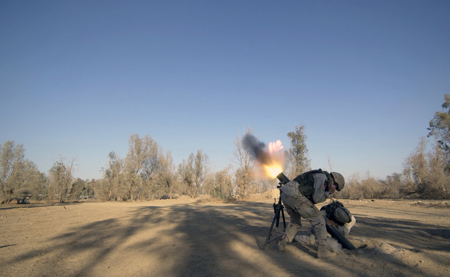 US Army (USA) Soldiers assigned to Charlie Troop, 1-4 Cavalry, 1ST Infantry Division, fire a 120mm M120 Battalion Mortar at Forward Operating Base Wilson, Iraq, during Operation IRAQI FREEDOM